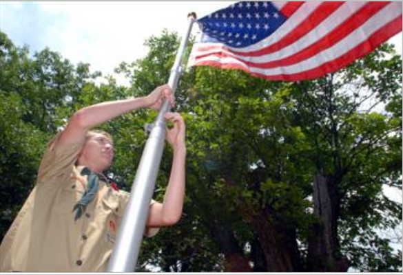 Eagle Scout Eric Hewitt raises an American Flag at the Pleasant Valley Cemetery